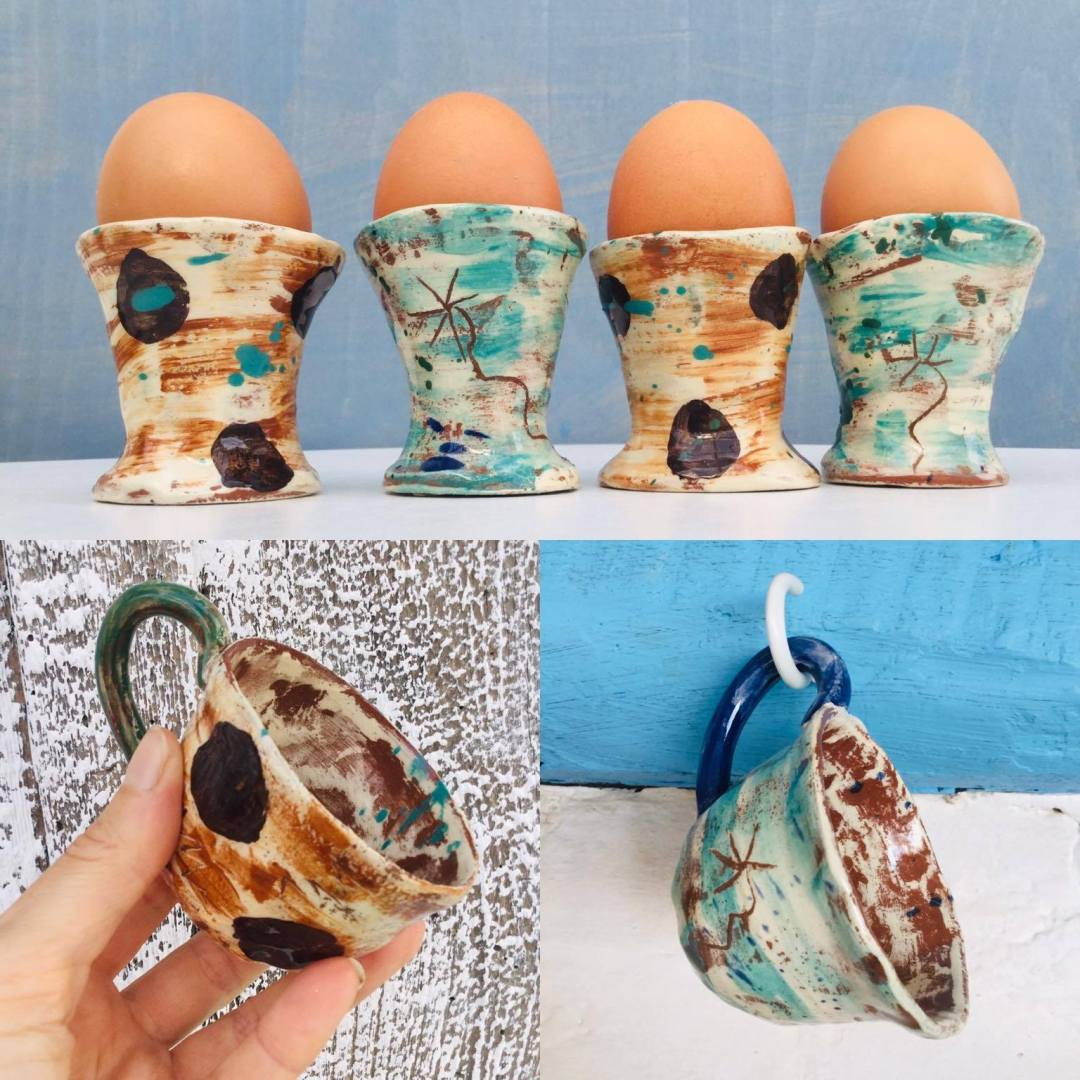 4 egg cups with real eggs and two espresso coffee cups in slipwarte by sarah monk ceramics