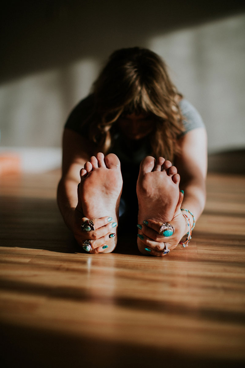 Sarah Silvas-Bernstein stretches and grasps her feet during a yoga pose in a studio