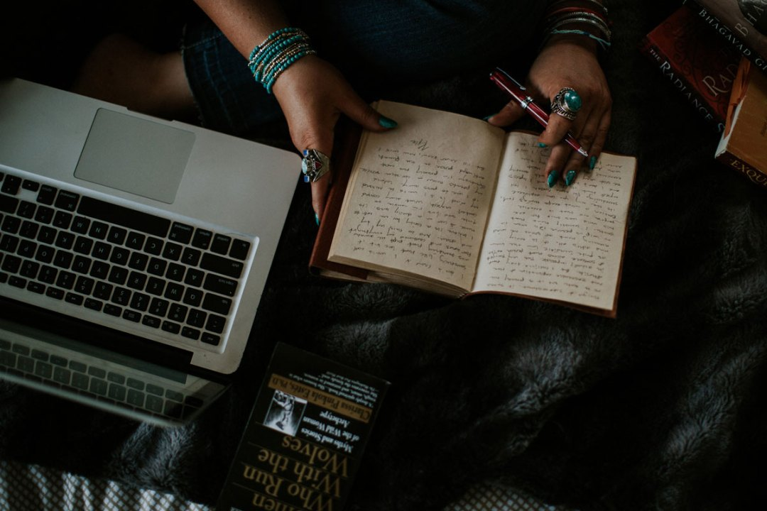 Image shows Sarah's hands with journal and pen next to a computer