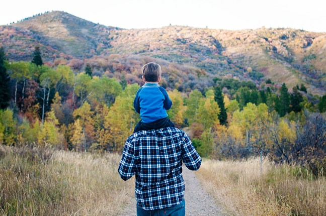 little boy on father shoulders in the mountains