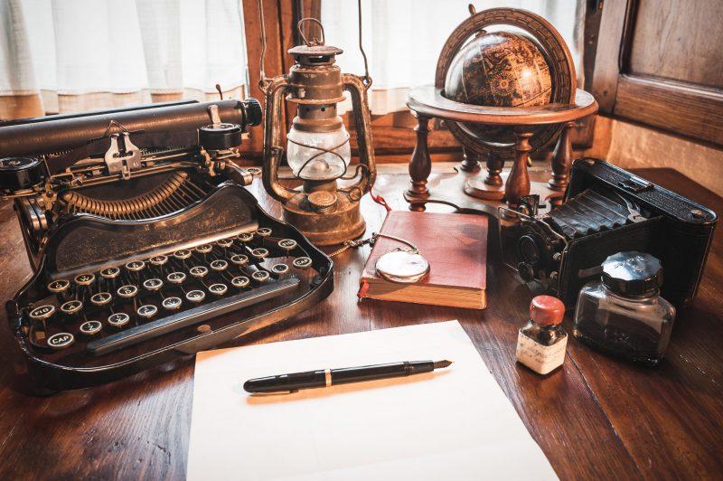 Old typewriter,  pen, lantern, and globe
