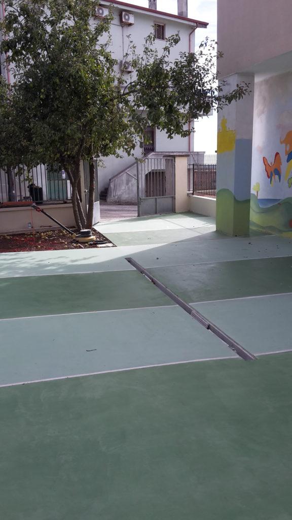 Piazzale esterno rivestito in microcemento verde presso asilo a paulilatino