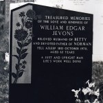 ornate grey gravestone with flowers carved in