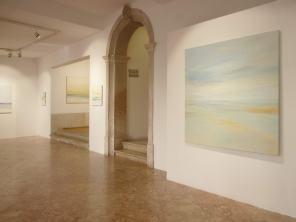 Vista de la sala principal a la sala interior Óleo 140 x 140 cm Memória entre Céu e Água; al fondo acuarelas
