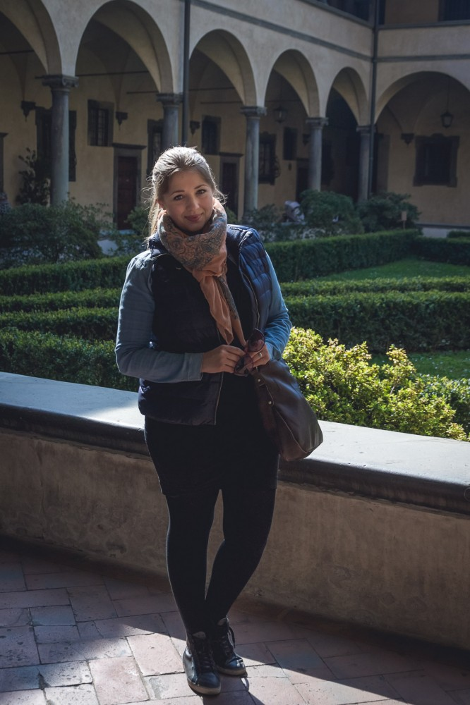 Julika's casual sightseeing look in Florence, Italy, in March: Black mini skirt and tights combined with a chambray shirt and a down vest and sneakers.