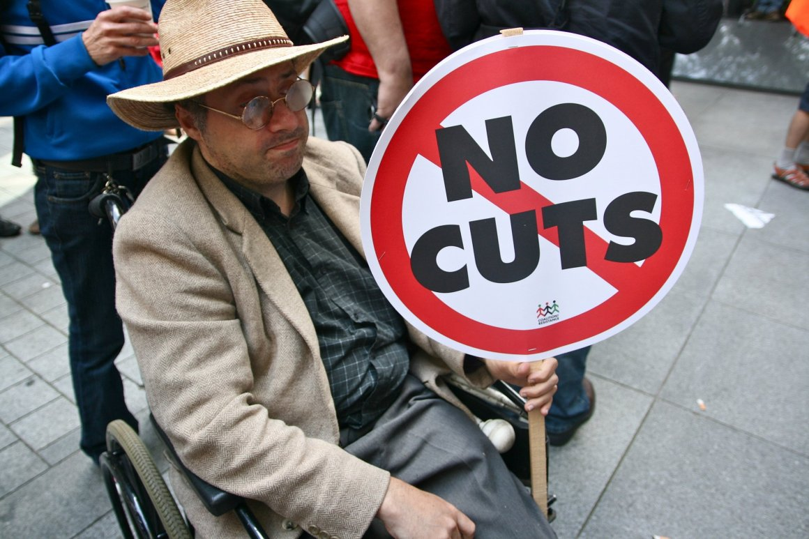 disabled-man-holding-no-cuts-sign
