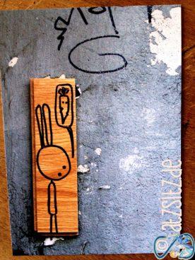 Postkarte, die Holzstück an einer Stadtwand zeigt. Auf das Holz ist ein Street Art Hase gezeichnet. Von MAENS