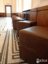 Braune Lederhocker mit lyrischem Aufdruck stehen entlang der Wand des Festsaals