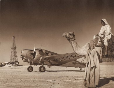 Oil well drilling rig with airplane and men with camel, ARAMCO (SMU Central University Libraries)