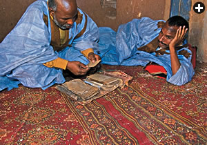 Soueid Ould Mohamed Bouyatou, left, and Limam Ould Abdel Mu'min show manuscripts from their archive, one of some 20 archives and libraries in the oasis with writings that date to as early as the 12th century.
