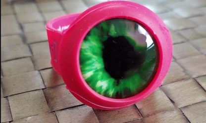 close up of green eyeball cabochon in red save a bowl