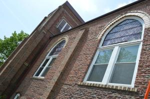 Arched brickwork and blue-toned stained glass windows are among the features of the structure, built as a Free Methodist Church in 1918. (photo/Cindy Hadish)