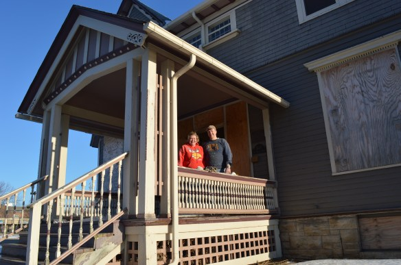 Dawn Stephens and Greg Young are shown on the porch of the Brewer House in Cedar Rapids. They hope to have the house moved about 10 blocks away in the coming month. (photo/Cindy Hadish)
