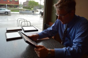 Robert Hach Jr. sits at Parlor City Pub & Eatery to look at photos from the early days of his family's saloon and bottling works after seeing the building demolished Monday, May 12, 2014, in Cedar Rapids. (photo/Cindy Hadish)