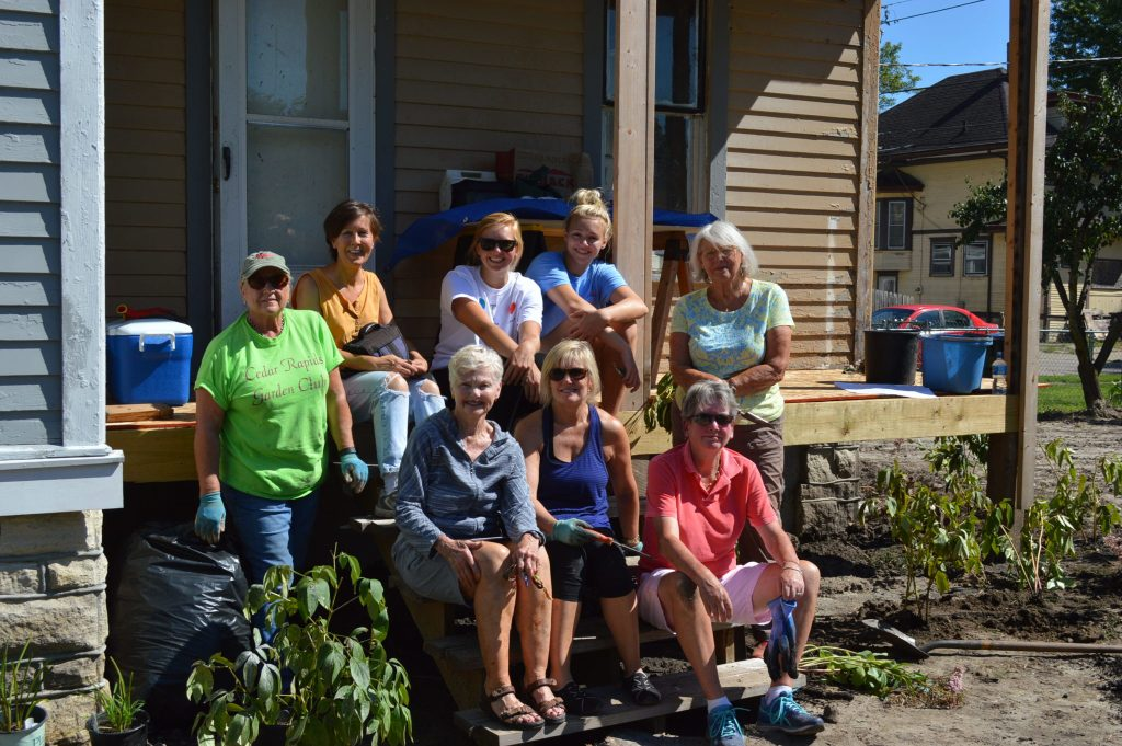 Members of the Cedar Rapids Garden Club, Cedar Rapids Washington High School's Interact Club and Save CR Heritage Board member Cindy Hadish gather on the back porch of the Frankie House during the landscaping day. (photo/Margaret Wolter)