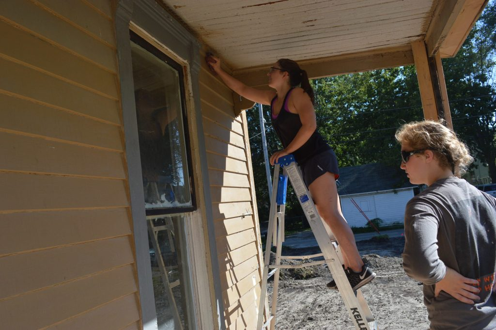 Members of Cedar Rapids Washington High School's Interact Club clean the porch at the Frankie House on Sunday, Sept. 18, 2016. (photo/Cindy Hadish)
