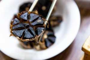 ail noir découpé avec baguettes chinoises saveeat