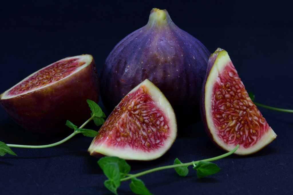 figue violette coupée en morceau sur fond noir save eat