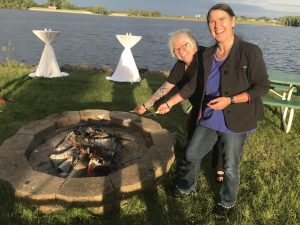 Deb and Becky toasting marshmallows over a campfire at RuralX 2019