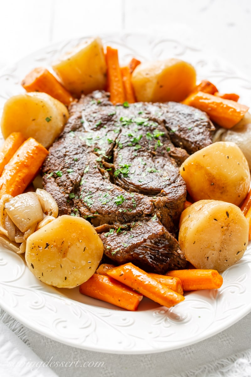 A platter with a slow cooker pot roast, potatoes and carrots