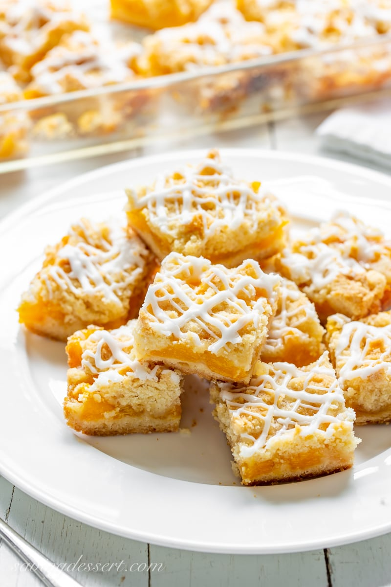 A plate of fresh peach crumb bars drizzled with icing