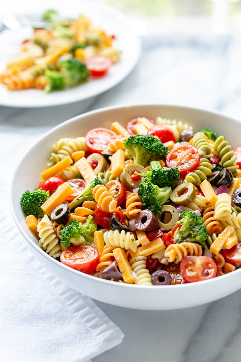 A bowl of fresh pasta salad with broccoli, olives and cheese