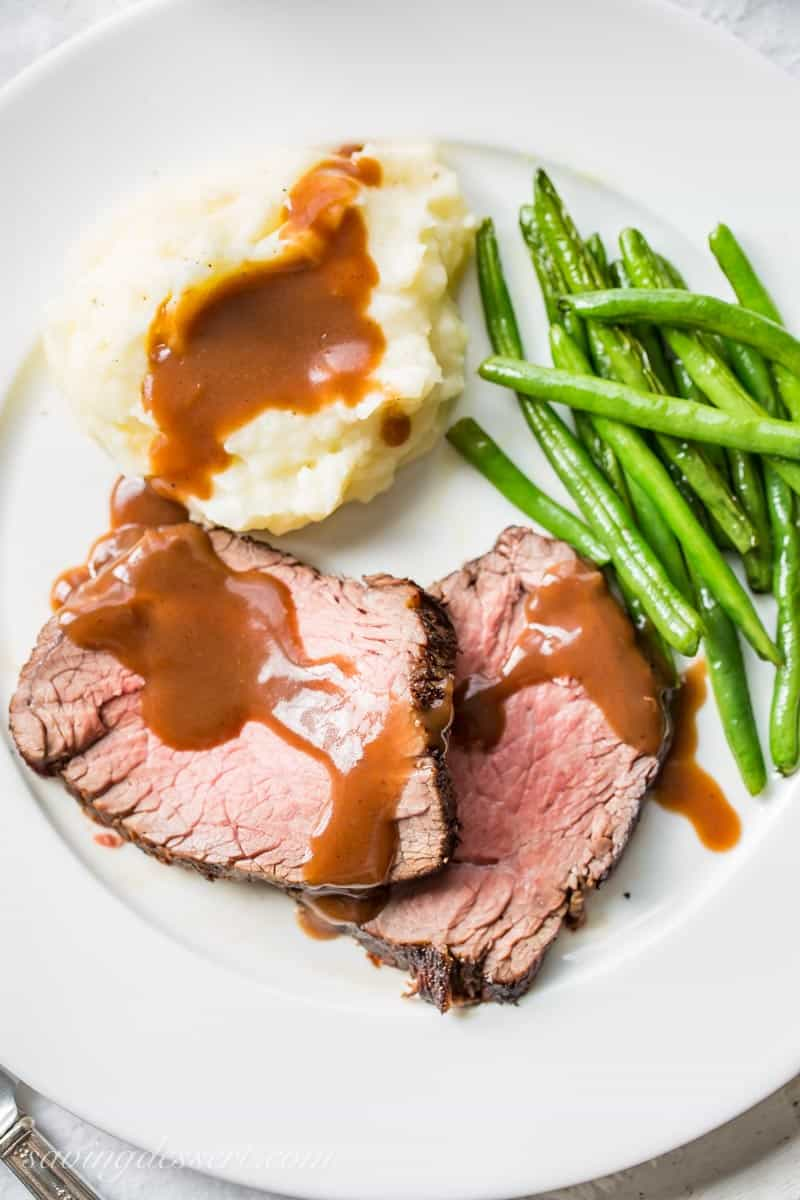 a plate with classic roast beef and gravy over mashed potatoes and green beans