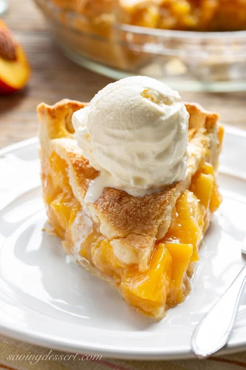 A slice of fresh peach pie with ice cream on top from savingdessert.com