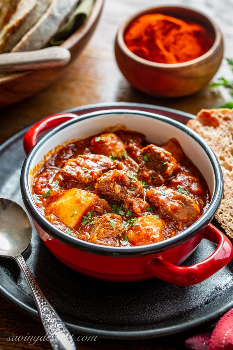 A bowl of Hungarian style Beef Goulash with potatoes and plenty of red sweet paprika. Served with bread and topped with fresh chopped parsley