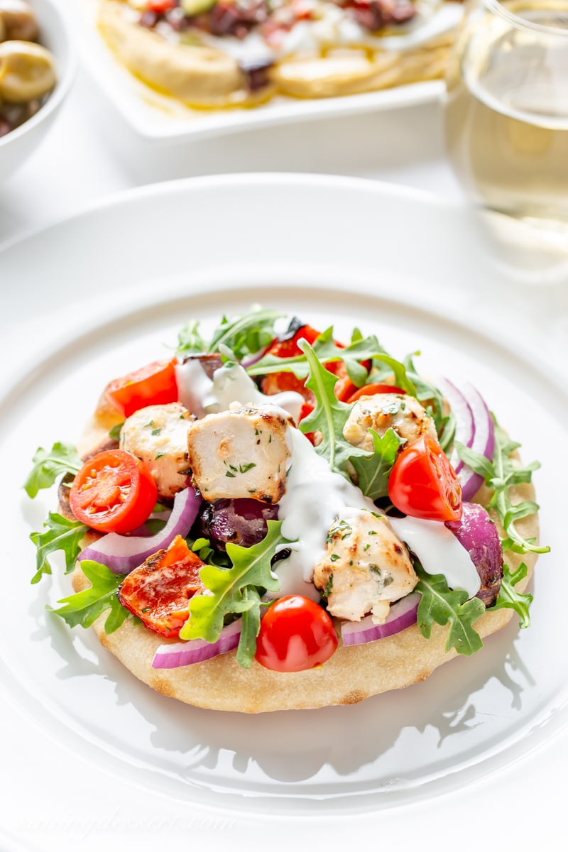 A grilled Greek Chicken pita pizza with arugula, onions and tomatoes