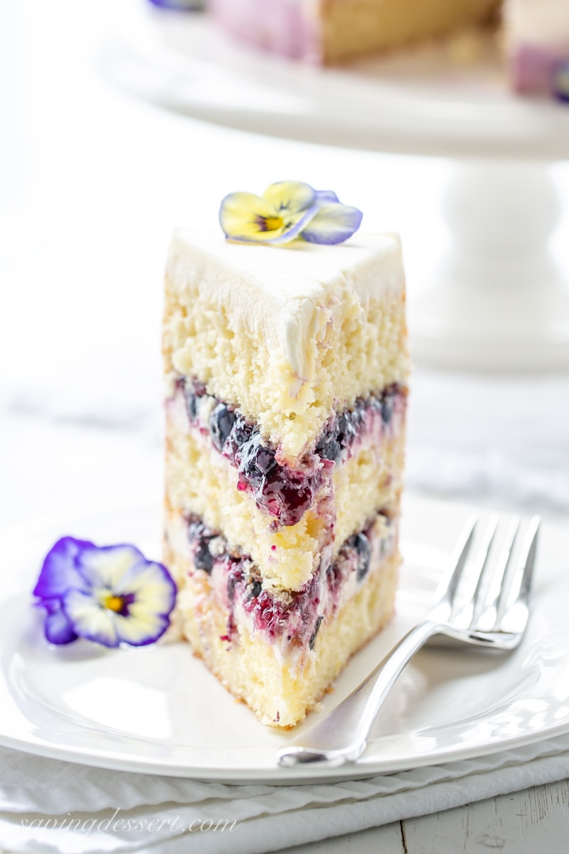 A tall slice of a three layer lemon cake with blueberry filling