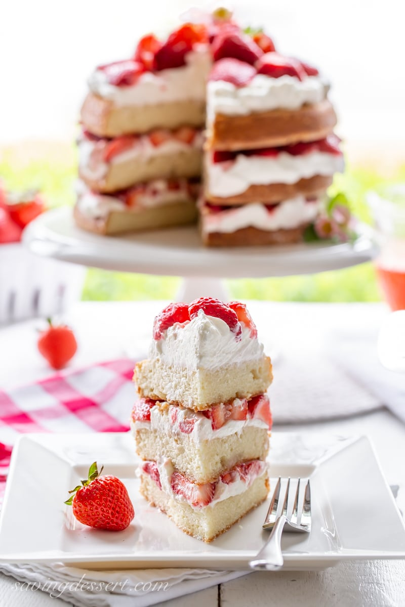 A three layer strawberry shortcake cake sliced into a towering wedge with fresh red ripe strawberries and layers of whipped cream