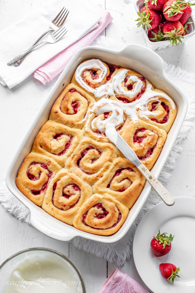 A pan of homemade Strawberry Sweet Rolls smeared with a cream cheese icing