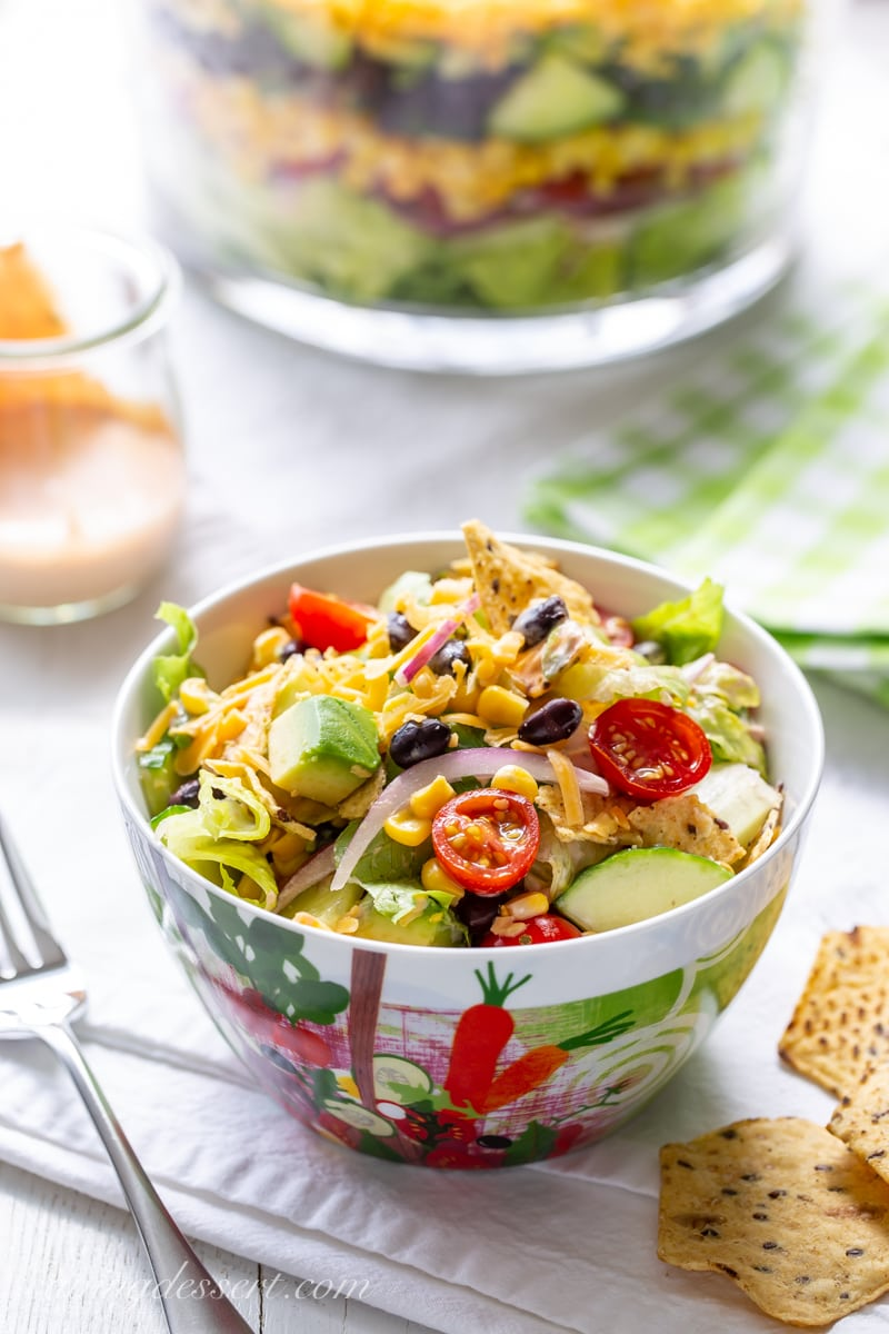 A bowl of Mexican Layered Salad with tomatoes, avocado chunks, cucumber and sliced red onion