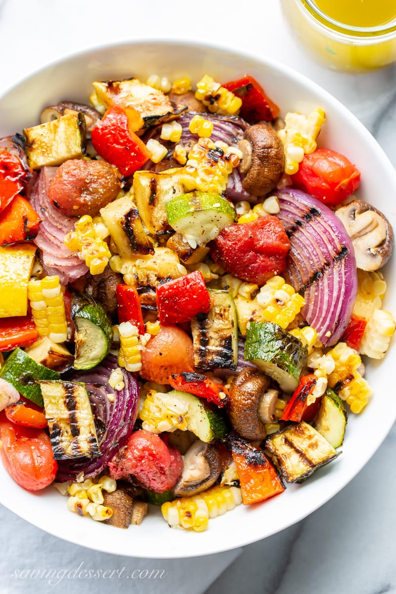 A bowl of chopped grilled vegetables with eggplant, onion, corn and squash