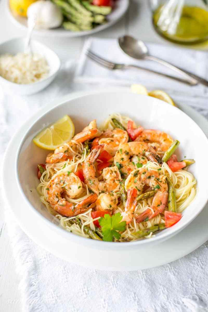 A bowl of shrimp scampi with asparagus and tomatoes over a bowl of angel hair pasta garnished with parsley