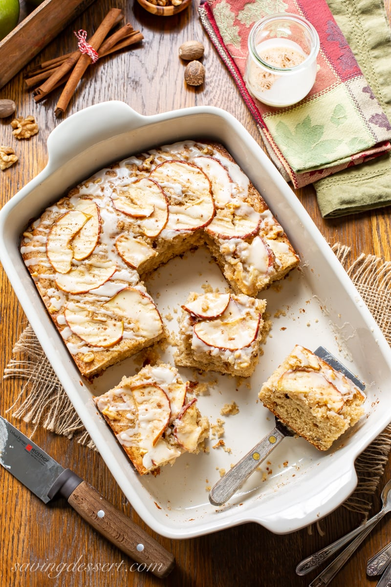 An apple sheet cake topped with apple slices cut into pieces.