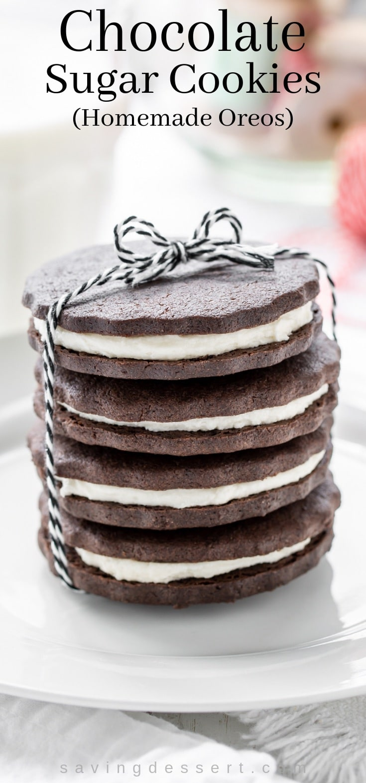 A stack of chocolate sugar cookies with a vanilla cream filing wrapped up with a black and white string