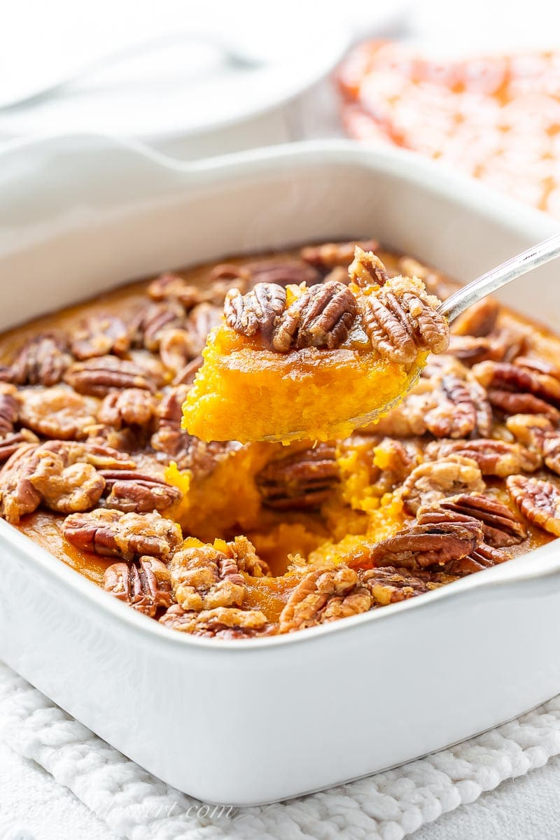 A butternut squash casserole in a spoon topped with pecans