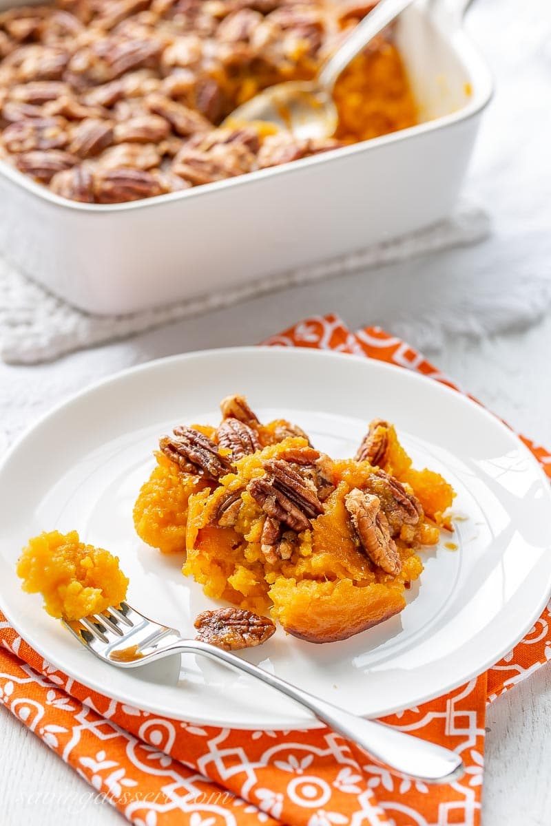 A plate of butternut squash casserole topped with pecans