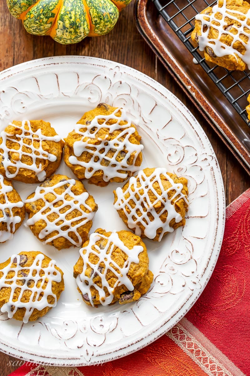 A plate of pumpkin chocolate chip cookies with a drizzled icing on top
