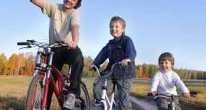 tata i djeca na biciklima