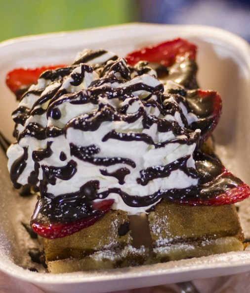 Belgian waffle with strawberries, whip cream and chocolate