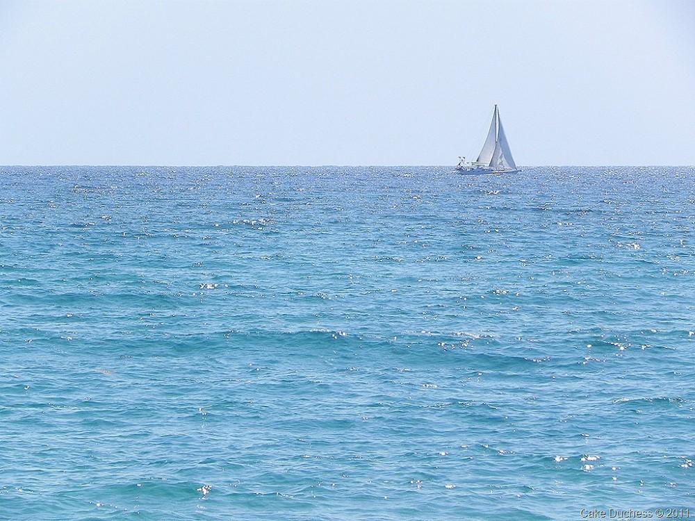 overhead image of sailboat on blue ocean