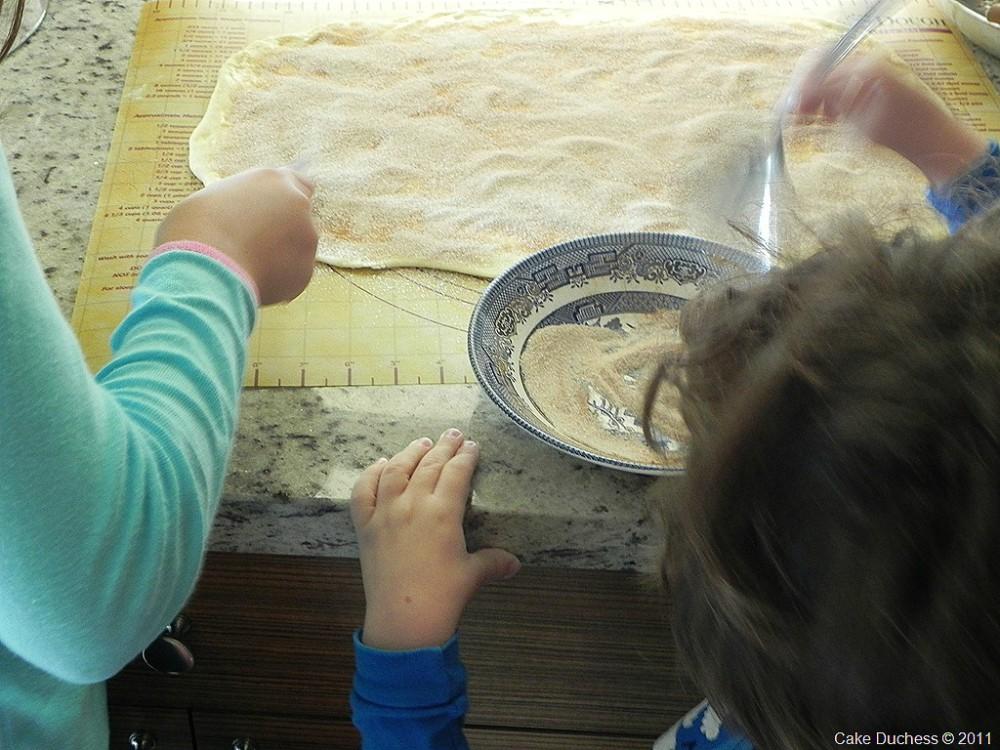 overhead image of kids sprinkling sugar on dough