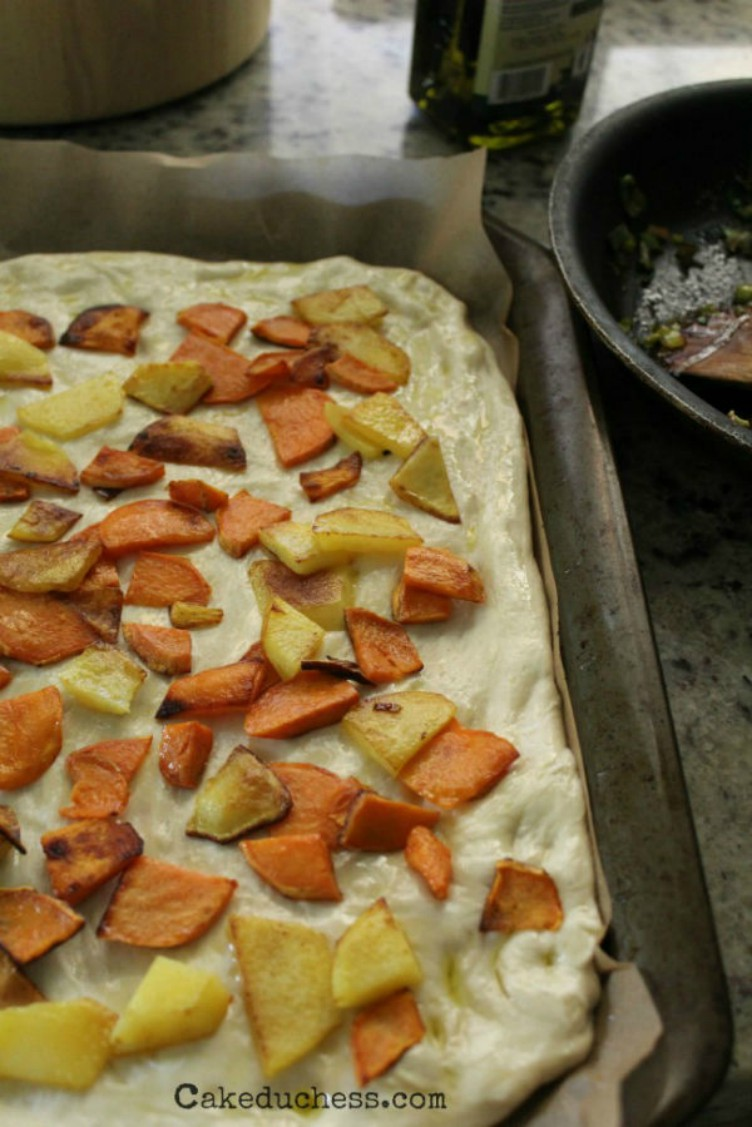 overhead image of large dough with potatoes on top