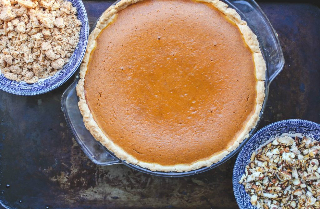 image of just baked pumpkin pie and crumbled amaretti cookies and chopped almonds