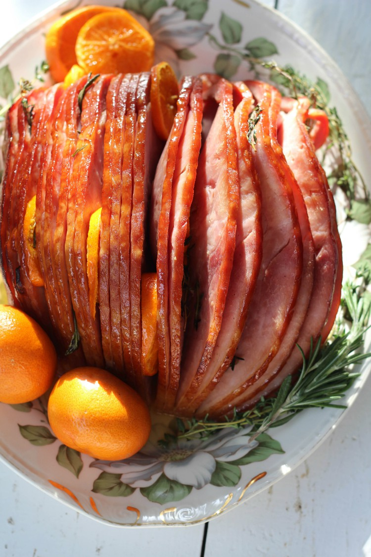 overhead image of spiral sliced ham and oranges on colored plate
