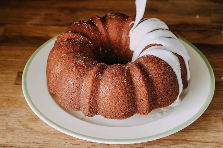 drizzling lemon bundt cake glaze on top of cake