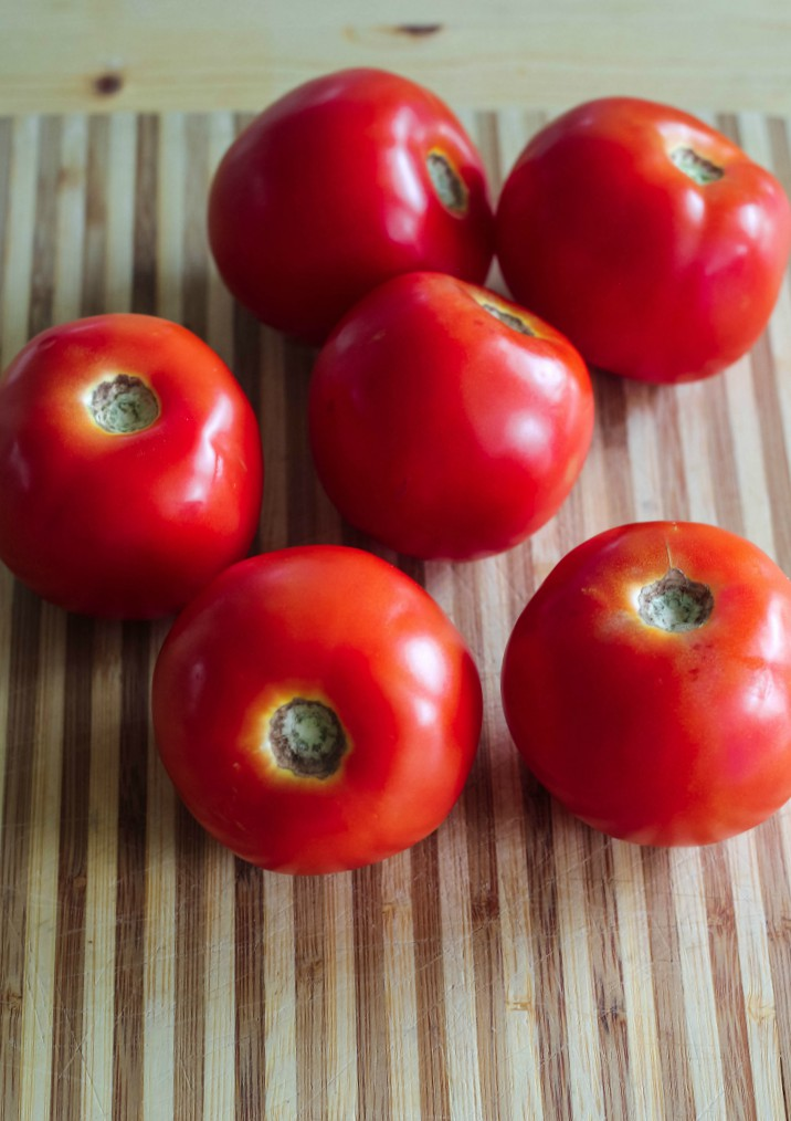 overhead image of tomatoes on wooden board